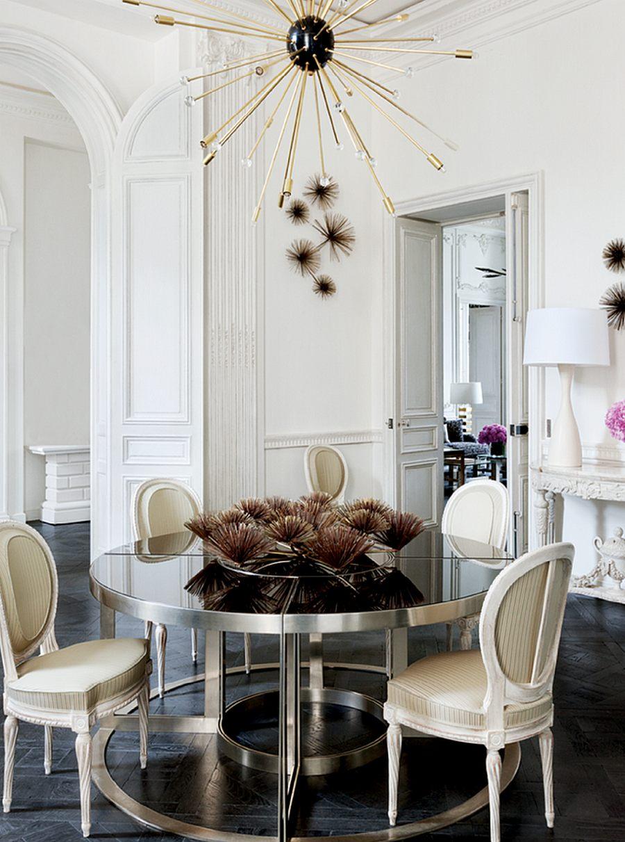 Металлическая современная круглая люстра, дополняющая декор на столе в большой гостиной